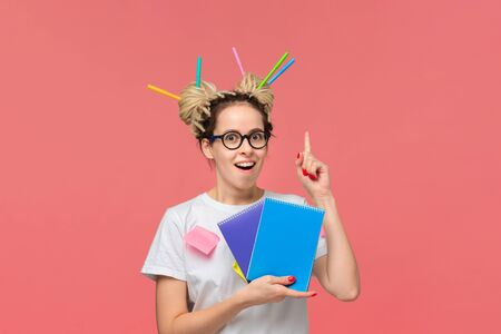 Smiling student in a white shirt and glasses, sticky notes on a shirt and colorful markers in dreads holding two notebooks and pointing with finger up at copy space. Concept of education and knowledge