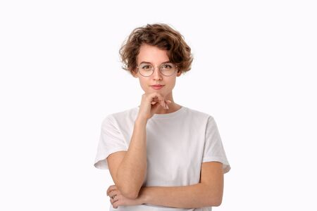 Thoughtful young woman in a white shirt and eyeglasses looking positively into a camera isloated over white background. Concept of thinking