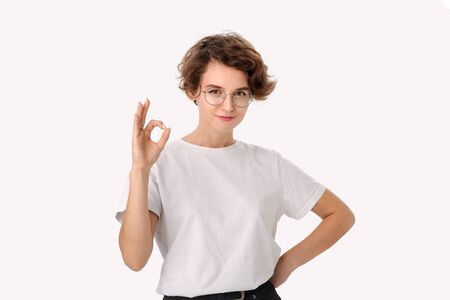 Pretty smiling woman in a white shirt and eyeglasses showing OK sign to express appreciation. Concept of like Stock Photo