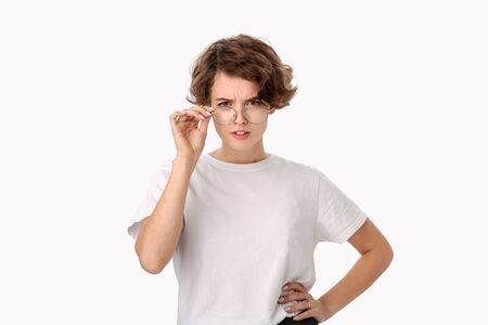 Suspicous young woman holding eyeglasses with one hand examining what she sees. Doubtful model