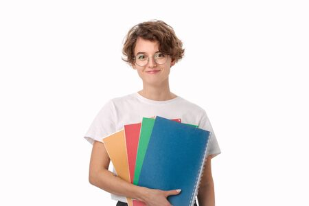Smiling young female student in a white shirt and eyeglasses holding colorful folders isolated over white background. Concept of education