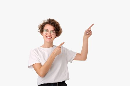 Pretty smiling woman in white shirt and eyeglasses pointing at copy space. Place for advertising