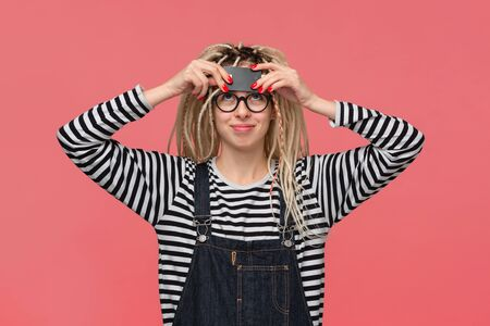 Teenager with dreadlocks in a striped shirt and jeans jumpsuit holding bank card. Pay with card.