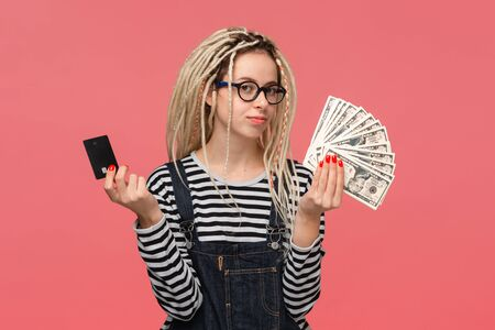 Teenager with dreadlocks in a striped shirt and jeans jumpsuit choosing between cash and bank card.