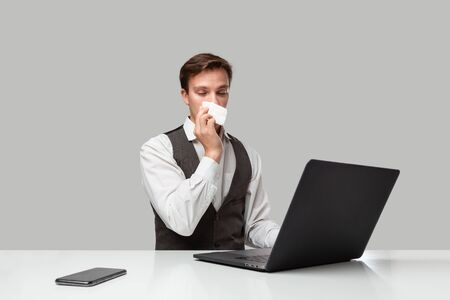 Businessman in a white t-shirt and grey vest working on a laptop in spite of running nose. Man looking at the camera. Time to take medical leave