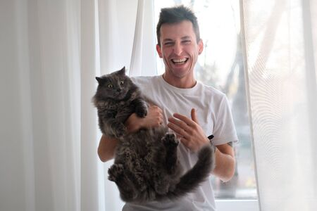 Young man in the white shirt and pajama is smiling holding fluffy cat which wants to run away. Man trying to pet the cat. Life with domestics animcals.