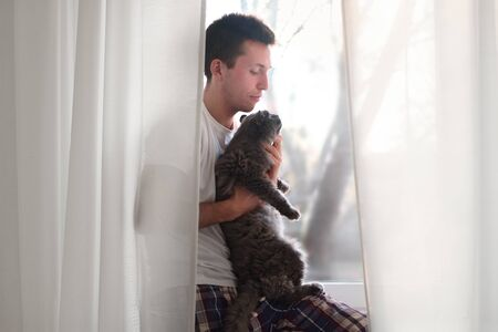 Young man in the white shirt and pajama petting grey fluffy cat. Life with domestics animcals. Stock Photo