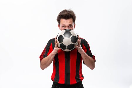 Confident soccer player in a red sportswear holding soccer ball infront of his face and looking at the camera. Concept of training for soccer cup qualification