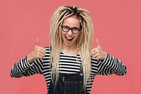 Beautiful young girl with dreadlocks in a striped shirt and jeans jumpsuit smiling holding thumbs up. Concept of like