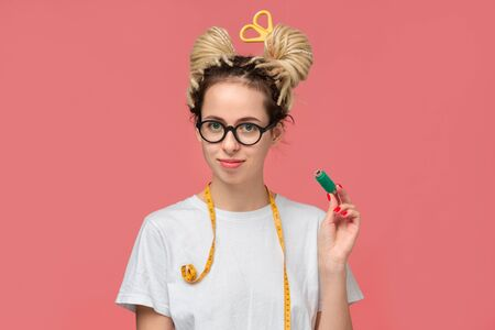 Smiling teenager in a white shirt and glasses and measuring tape on a neck and scissors in dreads. Being creative