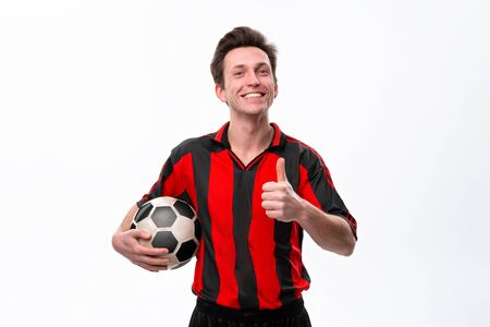 Excited soccer player in a red sportswear showing thumb up holding soccer ball. Enjoy training for soccer cup qualification