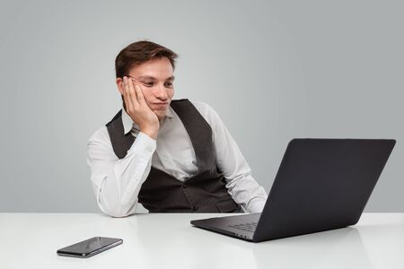 Businessman in a white t-shirt and grey vest is bored and looking at the screen of a laptop. Waisting time.