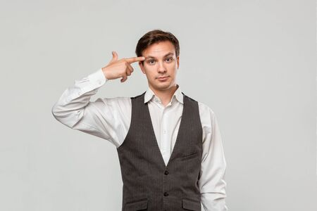 Young man in a white shirt and grey vest pointing with finger at the head. Concept of idea and thinking. Stock Photo