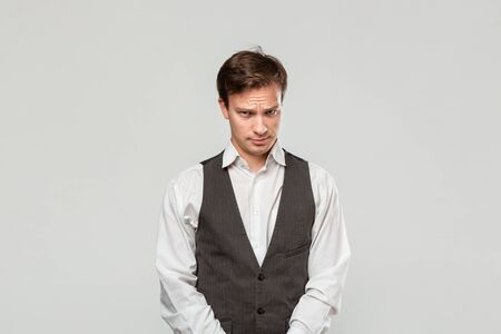 Young man in a white shirt and grey vest in high dudgeon over grey background. Stock Photo