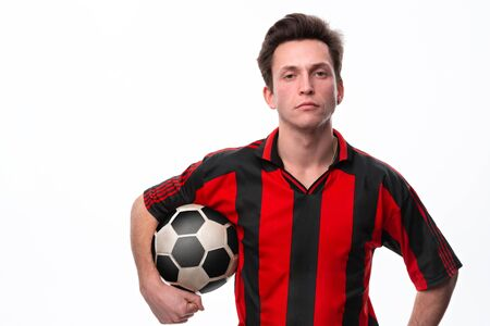 Confident soccer player in a red sportswear holding soccer ball and looking at the camera.