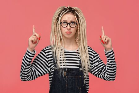 Beautiful young girl with dreadlocks in a striped shirt and jeans jumpsuit pointing with two fingers at copy space up. Place for advertising