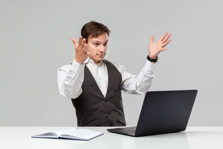 Businessman in a white t-shirt and grey vest is shocked checking information on a laptop sitting at the white table. Daily business routine.