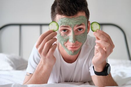 Young man in a white shirt with applied green cosmetic mask holding pieces of cucumber relaxing on a bed with white bed linen. Concept of wellbeing and facial treatment for men
