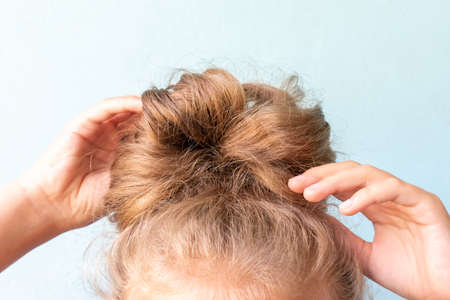 The girl straightens the disheveled bun on her head with her hands. Modern fast hairstyle. Blue background. Blond curly hair.
