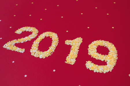 New 2019 year of confetti. The numbers of the next year in a sparkling yellow were placed on a red background.