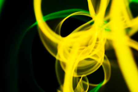 Yellow and green neon lines abstraction. Neon lights. Isolated on black background. Modern art.