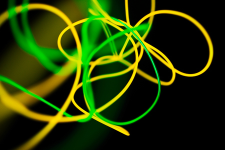 Yellow neon and green neon abstract. Neon lines. Isolated on black background. 写真素材