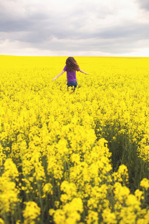 Young happy woman in canola field. Yellow field flowers. Beautiful stylish romantic. Colza, rapeseed.