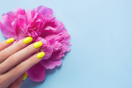 Stylish trendy female manicure. Neon yellow with pink peony flowers on blue background. Nail polish. Art manicure. Modern style.