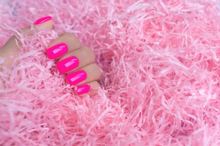 Stylish trendy female manicure. Neon plastic pink nails on confetti background. Nail polish. Art manicure. Modern style. Stock Photo