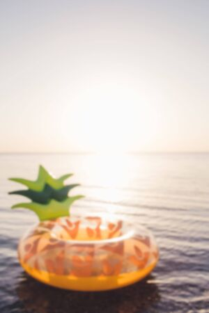 Abstract background with mattress pineapple on the background of the sea. Summer concept.