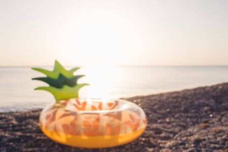 Blurred background with mattress pineapple on the background of the sea. Summer concept.