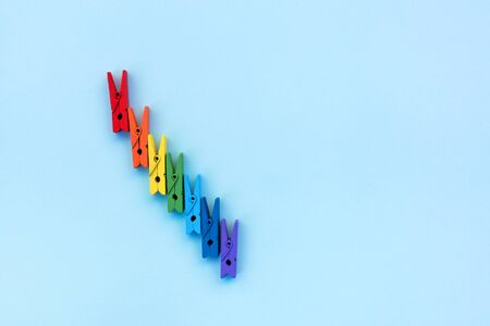 Many colored clothespins on a blue background. School concept. Minimalism.