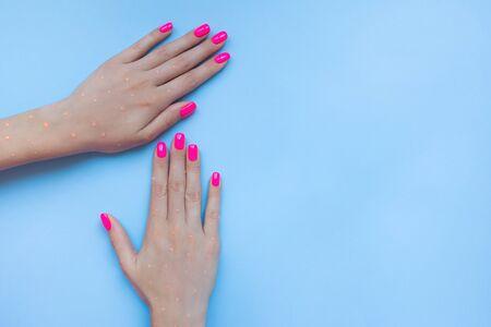 Stylish trendy female manicure. Beautiful neon plastick pink nails on blue background.