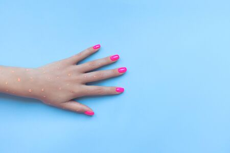 Stylish trendy female manicure. Beautiful neon plastic pink nails on blue background.