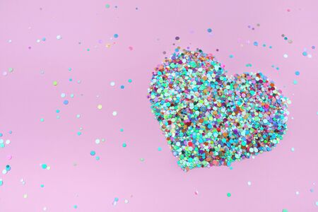 Confetti hearts on pink background. Copy space, top view. Valentines Day concept.
