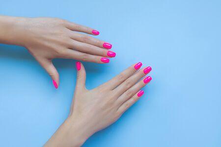 Stylish trendy female manicure. Beautiful neon plastic pink nails on blue background. Nail polish. Art manicure. Modern style.