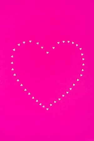 Pink confetti heart on bright pink background. Flat lay, top view, copy space.