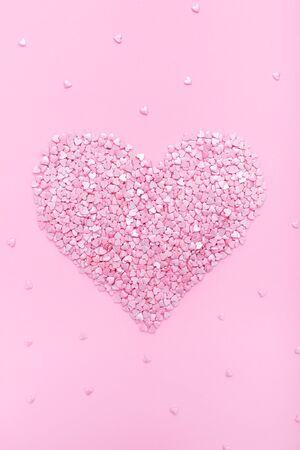 Fond rose. Coeurs roses sur fond rose. Coeurs arrose. Style plat. Vue de dessus. Fond doux. Confettis
