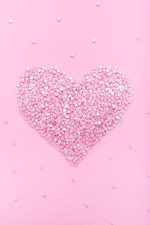 Pink background. Pink hearts on a pink background. Hearts sprinkles. Flat lay style. Top view. Sweet background. Confetti