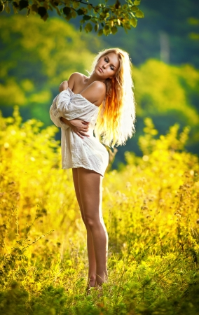 Portrait of a sensual young blonde female on field in sexy short white dress  Stock Photo
