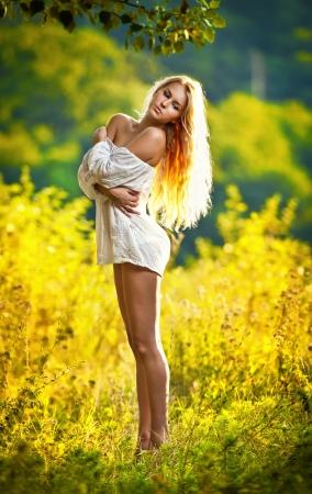 Retrato de una mujer rubia joven sensual en campo en sexy vestido blanco corto Foto de archivo