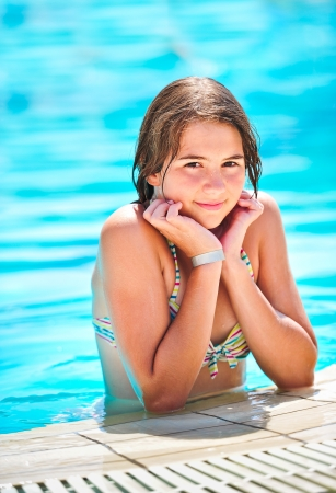 portrait of happy beautiful teen girl at the pool smiling at camera  Teen girl surrounded by aqua pool water  photo
