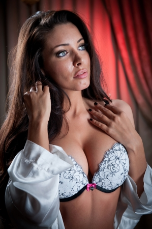 21620830: attractive and sexy brunette with white bra looking one side Portrait of young woman wearing white bra in classic scene Beautiful and sexy girl wearing white lingerie