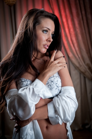 21620831: attractive and sexy brunette with white bra looking one side Portrait of young woman wearing white bra in classic scene Beautiful and sexy girl wearing white lingerie