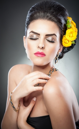 Hairstyle and Make up - beautiful female art portrait with yellow roses Elegance  Genuine Natural brunette with Flowers  Portrait of a attractive woman with beautiful eyes and flowers in her hair   photo