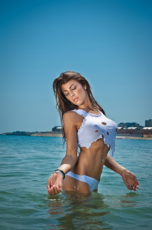young sexy brunette girl in white bikini and wet t-shirt playing in the water Sensual attractive woman in water wearing bikini and long legs  Woman with perfect body relaxing and playing on the beach  photo