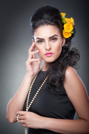 Hairstyle and Make up - beautiful female art portrait with yellow roses and beads Elegance  Natural brunette with flowers  Portrait of a attractive woman with beautiful eyes and flowers in her hair   photo