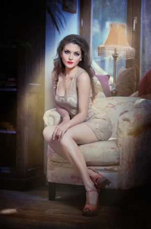 Young beautiful luxurious woman sitting on a vintage couch  Beautiful young woman in a luxurious classic interior  Seductive woman in luxury manor, vintage style Stock Photo - 22612445