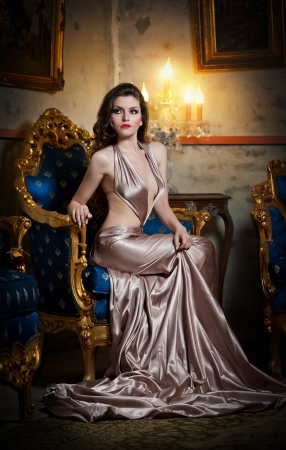 Young beautiful luxurious woman in long elegant dress  Beautiful young woman in a luxurious classic interior  Seductive brunette woman in luxury manor, vintage style photo