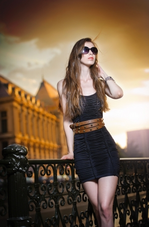 Fashion model on the street with sunglasses and short black dress Fashionable girl with long legs posing on street High fashion urban portrait of young, slim, beautiful model photo